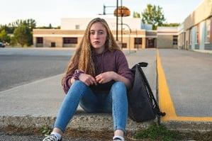 Teen girl waiting outside school