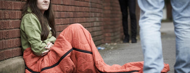 Girl in sleeping bag on street