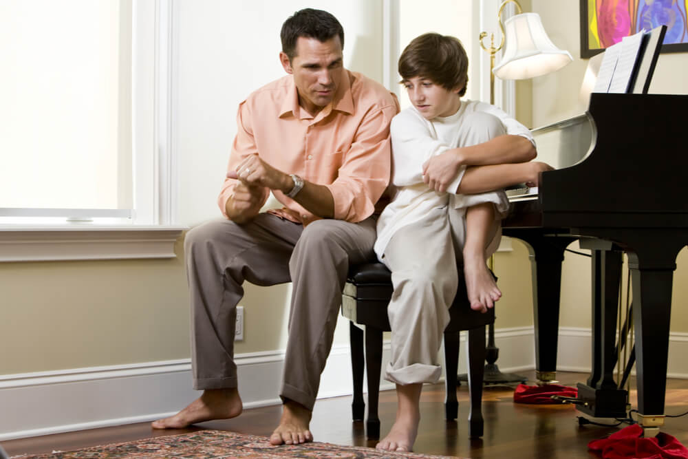 Serious father talking to teenage son at home by piano