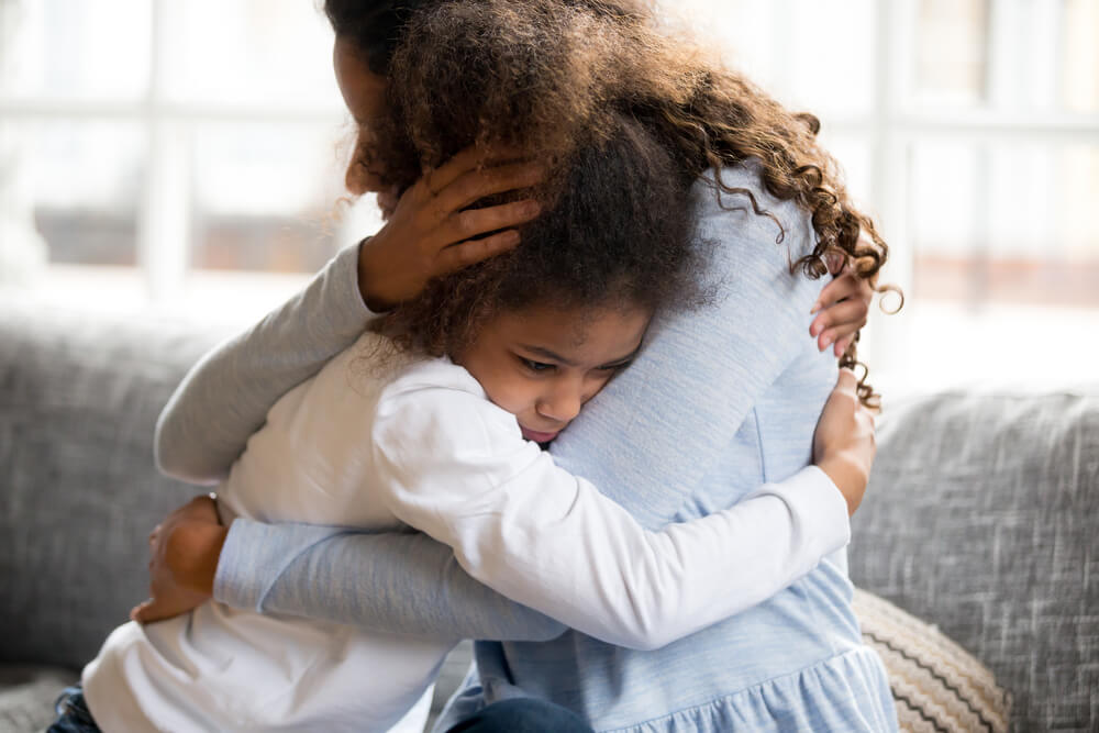 loving mother supports disappointed daughter sympathizing, embracing little girl