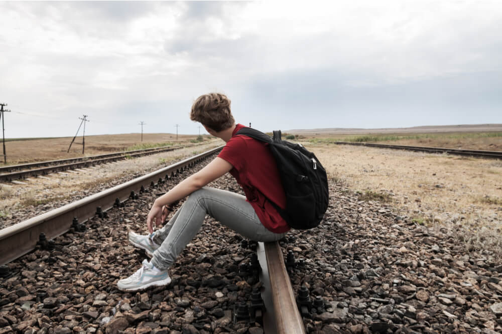 Teen boy skipping school, sitting on railroad tracks with backpack on