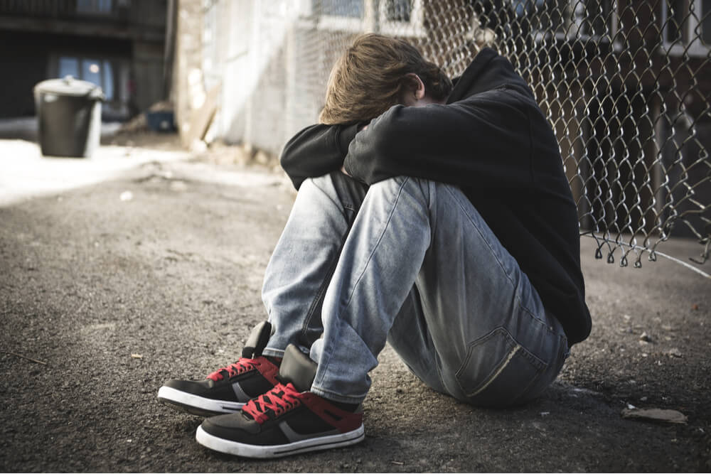 teenager with his back against the fence, head down, considering suicide